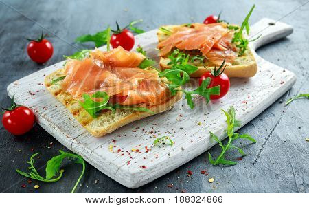 Homemade grilled toast with Smoked Salmon, rucola, tomatoes on white board. healthy breakfast.