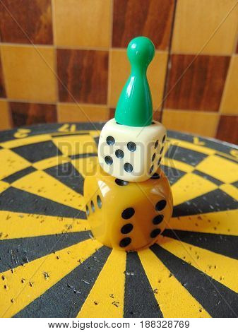 dice tower with play figure on top with chess board background