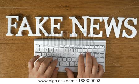 Fake News title on top of hands typing on keyboards