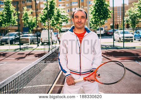 Portrait of tennis player man, looking at camera and holding tennis racket , front view. Sporty player on the tennis court at sunny day