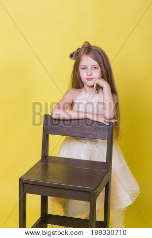 Portrait of a cute teenage girl on a yellow background on the chair.