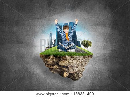 ECO concept floating island and happy kid boy with book sitting on it