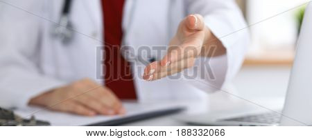 Female medicine doctor offering helping hand in office closeup. Physician ready to examine and save patient. Friendly and cheerful gesture. Medical cure and tests advertisement concept