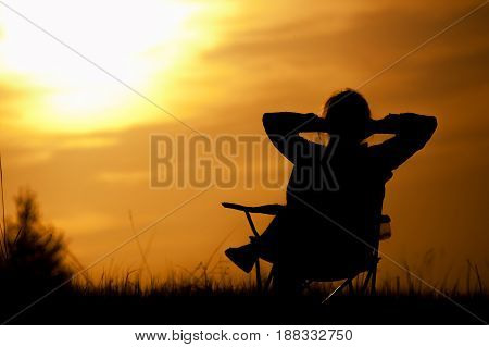 Silhouette of relaxed woman enjoying sunset time, sitting in the chair outdoors. Travelling and vacation concept.
