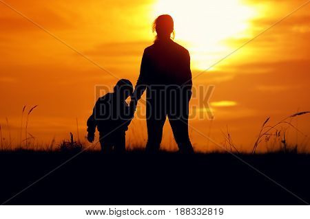 Happy family relationship. Silhouettes of young mother and little son standing together, holding hands and watching sunset.