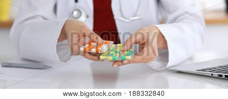 Female doctor hand holding pack of different tablet blisters at workplace closeup. Panacea, life save service, prescribe medicament concept