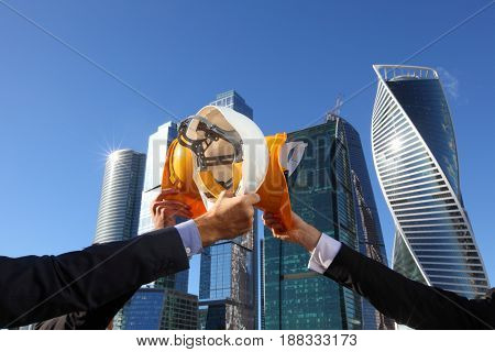 Group of business people clinking their helmets as a success on skyscrapers background construction finished concept
