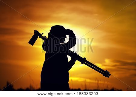 Silhouette of professional female photographer holding camera and tripod, looking into the distance at sunset time. Travelling and tourism concept.
