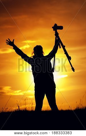 Silhouette of female photographer holding photo camera and tripod at the background of setting sun. Happy woman raising hands to the sky. Travelling and tourism concept.