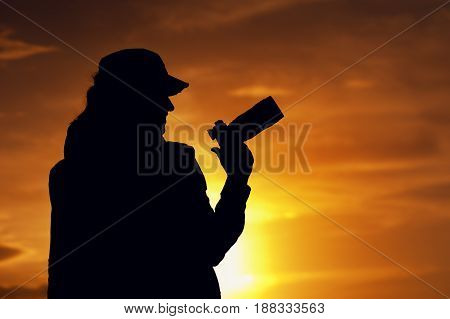Silhouette of professional female photographer taking pictures with camera against setting sun. Happy smiling woman watching sunset. Travelling and tourism concept.