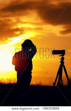 Silhouette picture of little boy standing with photo camera and tripod against setting sun. Kid photographer.