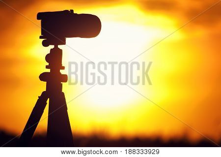 Silhouette of modern camera standing on tripod against setting sun. Travelling and tourism concept.