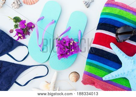 Summer beach fun - sandals with swimming suit, beach towel and starfish