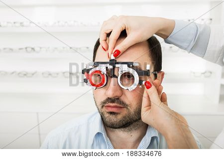 Man patient check vision with optometrist trial frame at ophthalmological clinic