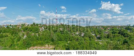 Panoramic view of urban outskirts located on a hill in the background of a radio transmitting antenna
