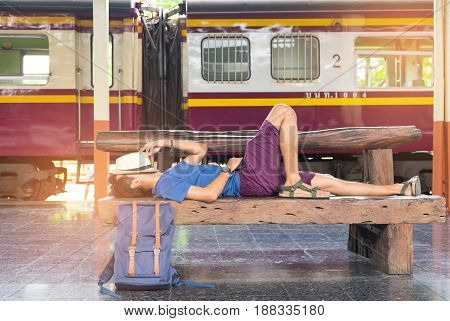 Travelers slept on chairs while waiting for the trainHat on face with luggage on the side.