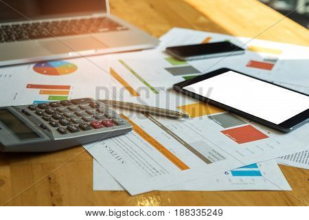 Business accessories,Laptop calculator tablet smart phone pen with graphs on office desk.