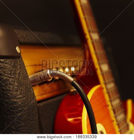 Combo for electric guitar with guitar on the black background. Shallow depth of field low key close up. Focus on input jack.