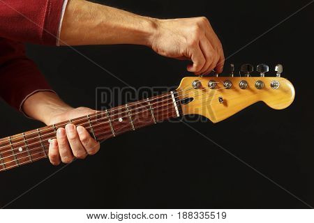 Hands of guitarist tunes the electric guitar on the black background