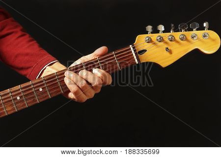 Hand of rock guitarist behind the electric guitar neck on the black background