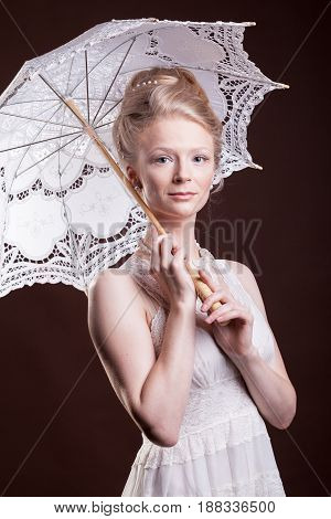 Gorgeous woman in vintage dress holding a lace umbrella. Rich and vintage. Luxury and elegance. Studio photo