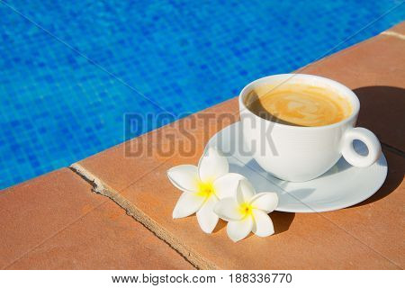 white cup of coffee on the edge of pool with cool water