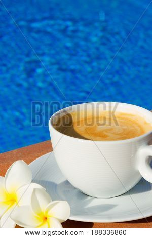 white cup of coffee close up on the edge of pool with cool water