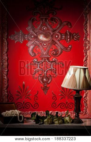 Rich red victorian interior with a lamp on fireplace. Luxury annd vintage