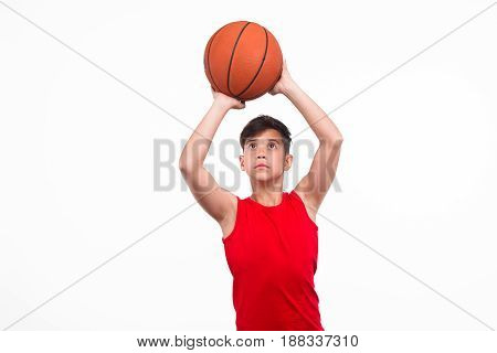 Young male teen athlete throwing a ball for basketball isolated on white.