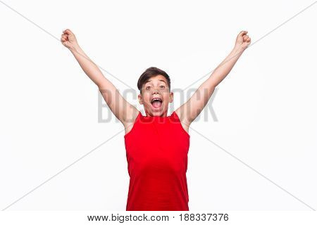 Surprised young male teen looking at camera and shouting expressing happiness.