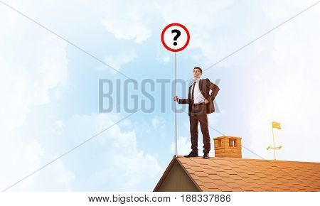 Young businessman with roadsign on roof edge. Mixed media