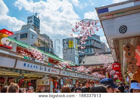 Tokyo, Japan - April 19, 2017: busy people walking in spring sakura on Nakamise Dori, street with food and souvenirs shops. Kaminarimon Gate of Senso-ji Buddhist Temple, Asakusa area, on background.