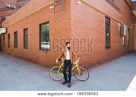 Young handsome man with a beard against the backdrop of a brick wall sits on a bicycle