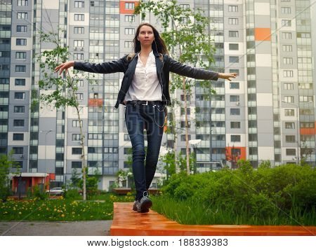 Young girl easy to walk the parapet. Long hair beautiful figure. The background high-rise apartment building