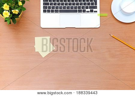 Office table with laptop, notepad and coffee cup. View from above with copy space.