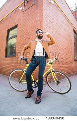Young Stylish Man With A Beard In Sunglasses Sitting On Bicycle On A Brick Background