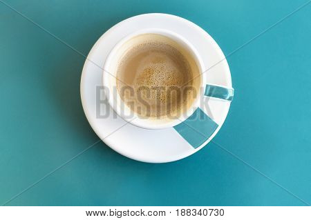 A photo of a white cup of coffee, shot from above on a turquoise background texture with copy space