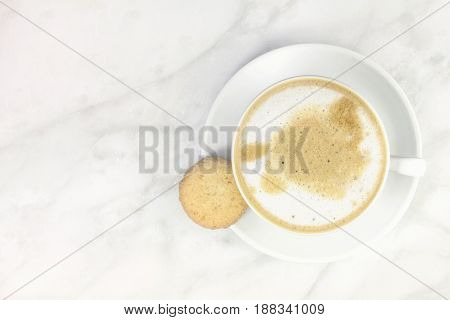 A high-key photo of a cup of coffee with milk with a butter cookie, shot from above on a light texture for copy space