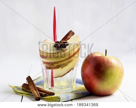 Detox water with apple cinnamon and anise on a white wooden background