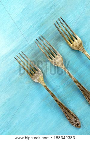 An overhead photo of three vintage forks on a vibrant turquoise wooden background texture. A restaurant menu or special offer banner design template with a place for text