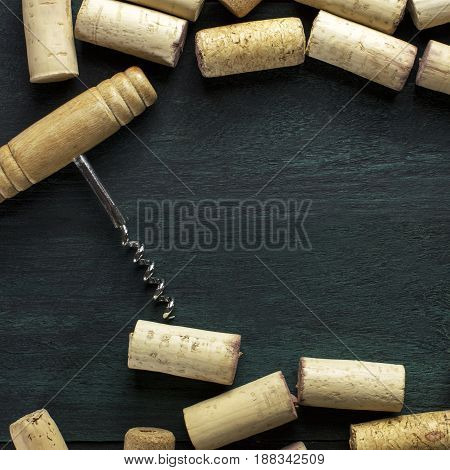Many wine corks and a vintage cork screw on a dark wooden background texture with copyspace. A square design template for a tasting invitation or restaurant menu