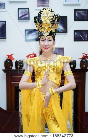 beautiful asian girl in a traditional yellow chinese stage costume standing near the wall with pictures and fireplace