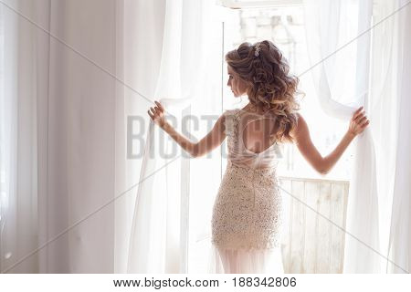 bride in a beautiful wedding dress stands in a white room by the window