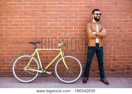 Handsome Young Bearded Man While Standing Near His Bicycle Against The Brick Wall