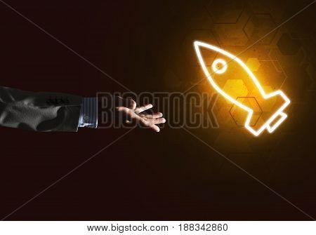 Rocket glowing icon and businessman hand on dark background