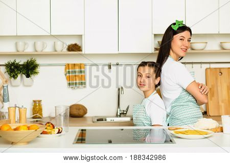 Family holidays. Mom and daughter in the kitchen, stand and look at the camera. Cooking with family