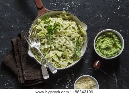 Vegetarian pasta farfalle with broccoli pesto in a cast iron skillet on the dark table top view