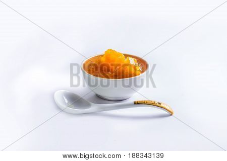 A thick pumpkin jam in a saucer and a porcelain spoon. Folk recipes. Sweet dessert. Healthy food. Close-up.