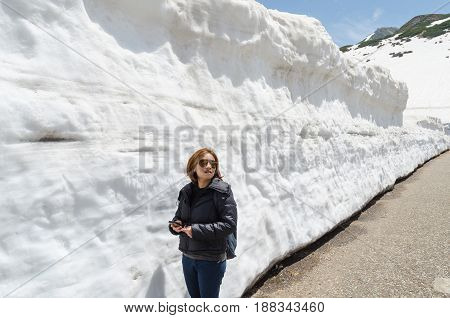 Female traveler and snow wall at japan alps tateyama kurobe alpine route