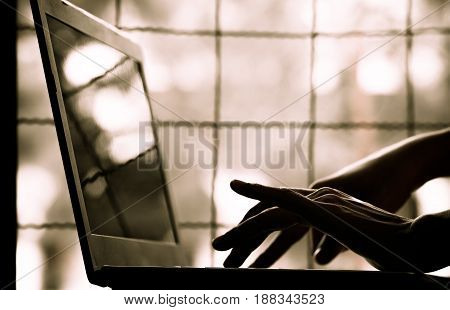 silhouette black and white of anonymous hacker typing on keyboard of laptop for remotely hacking and receiving personal information near window Payment Security Concept